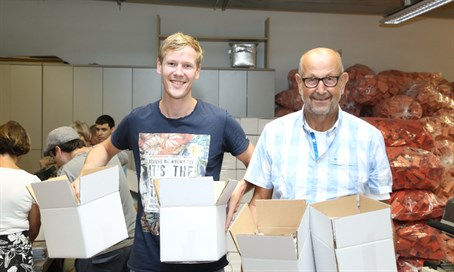 Lev Haolam volunteers packing boxes to be sent out to customers