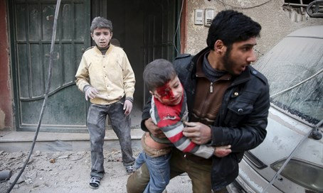 Syrian man carries boy injured by regime shelling