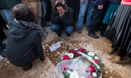 Mourners place flowers on Dafna Meir's grave