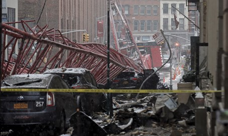 A construction crane is seen on top of cars along the street in downtown Manhattan, New Yo