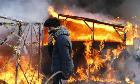 Migrant in front of burning shelter in the Calais 'Jungle'