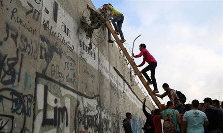 Arabs climb over Jerusalem security barrier (file)