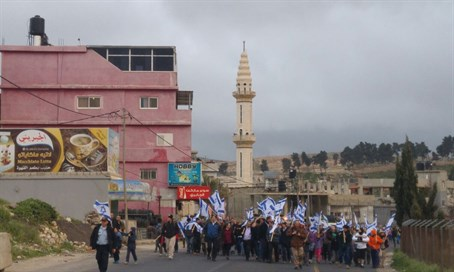 Protest march in Judea with mosque in background