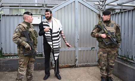 Soldiers guarding a staff member at a Chabad school in Paris, Nov. 16, 2015.