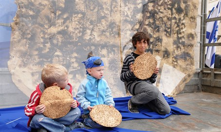 Israeli children eat matza at a Meir Panim center