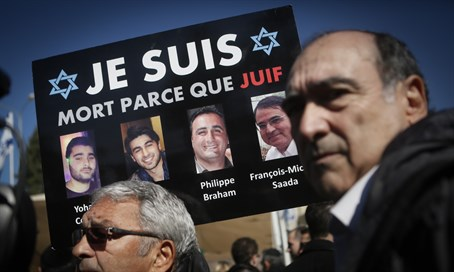 Mourners in Jerusalem hold pictures of Jewish victims of 2015 Paris attacks