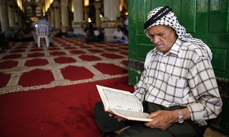 Muslim man reads the Koran during Ramadan at Al Aqsa Mosque