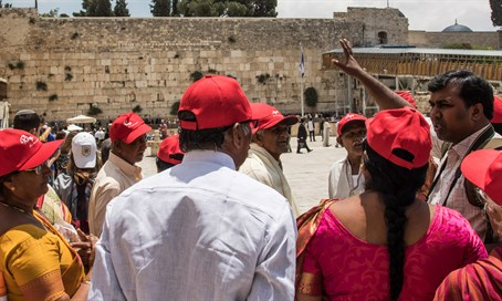 Tourists listen to guide near the Western Wall
