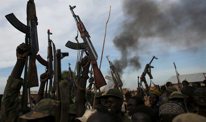 Rebel fighters in Sudan holding up rifles