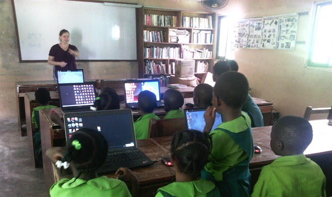 A Project TEN volunteer runs a computer class for children in a fishing village in Ghana