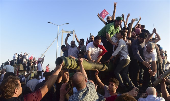 Government supporters celebrate atop tank seized after failed coup