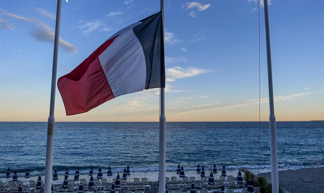 French flag flying at half mast at an empty beach on the Promenade des Anglais