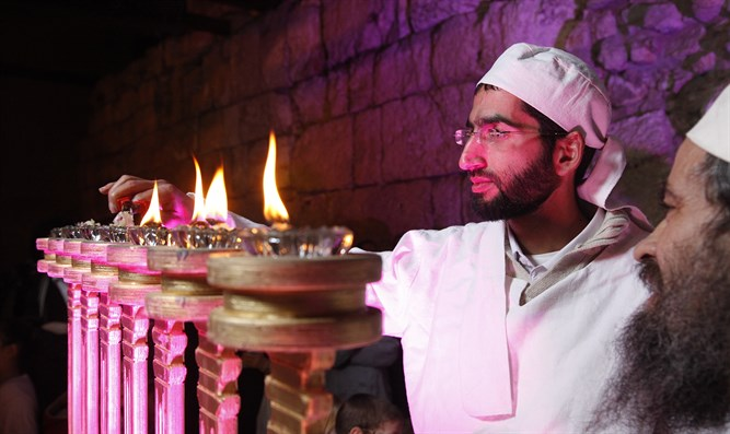 Kohen lights menorah in priestly garments