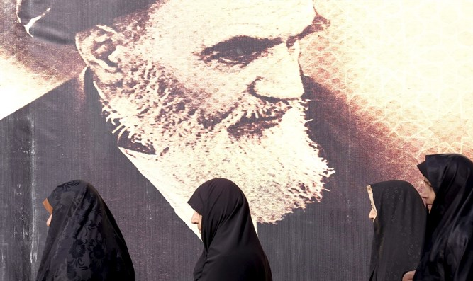 Iranian women by a poster of Ayatollah Khomeini