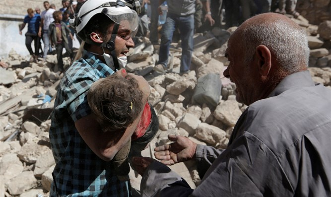 A child's body is carried away fromthe site of a regime bombing in Idlib, Syria