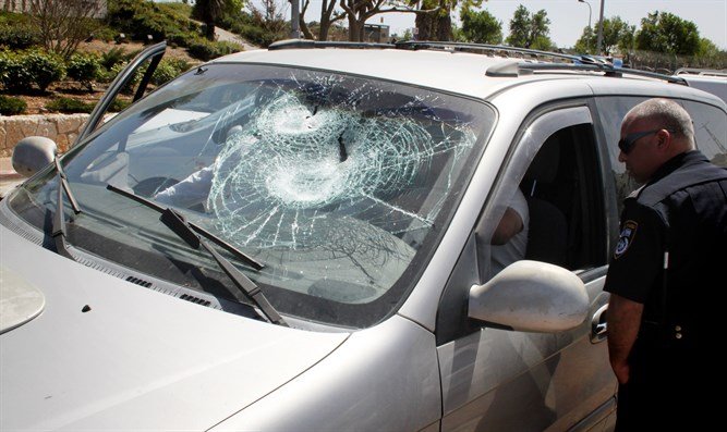 Car windshield smashed in rock attack (illustrative)