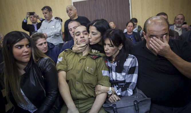 Elor Azariya sits with his family