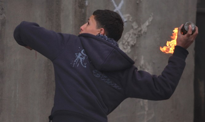 Arab youth hurls a firebomb during anti-Israel riot (file)