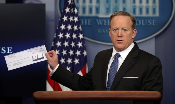 Spicer shows Trump's check that was donated