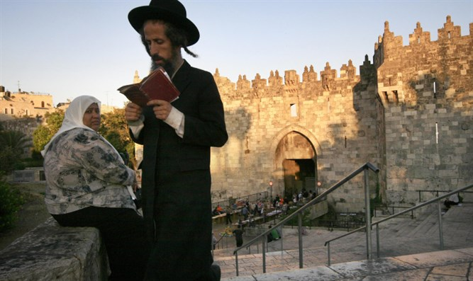 Haredi man passes Arab woman near Damascus Gate in Jerusalem