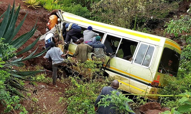 Rescue workers attempt to rescue victims of Tanzania bus crash.
