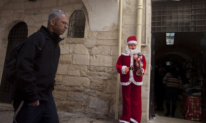 A Jewish man walks next to a Santa Claus doll for Christmas in a shop in Jerusalem's Old