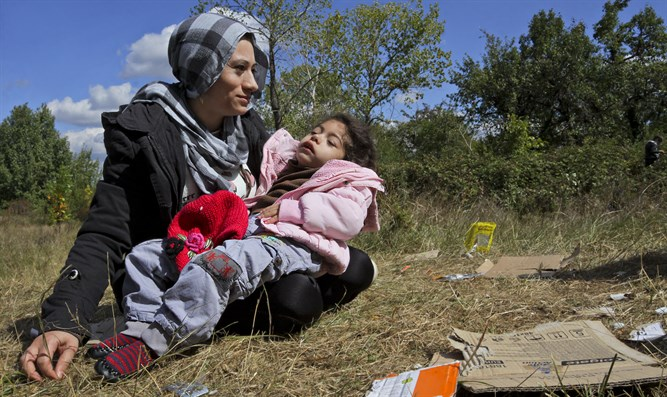 Syrian mother holds her sick child
