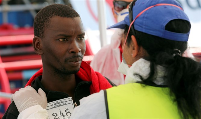 Medical staff member checks the condition of migrant as they arrive at Crotone harbour. It