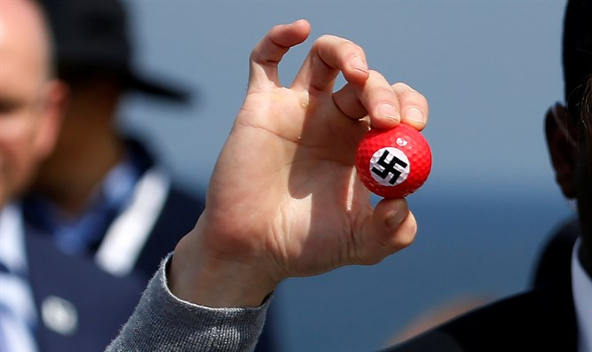 Protester holds golf balls with swastika at Trump press conference, Turnberry Golf course,