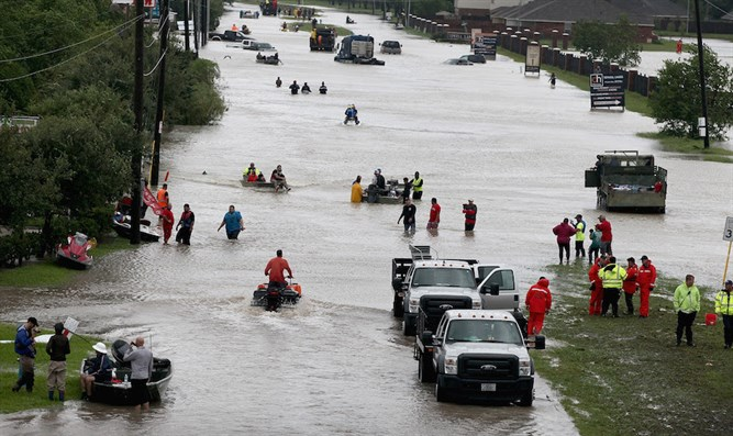 Houston residents and rescuers make their way out of a flooded neighborhood after it was i