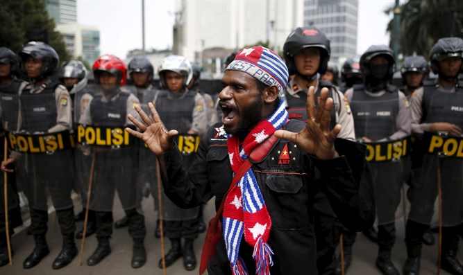Activist shouts near police line during rally commemorating West Papuan independence