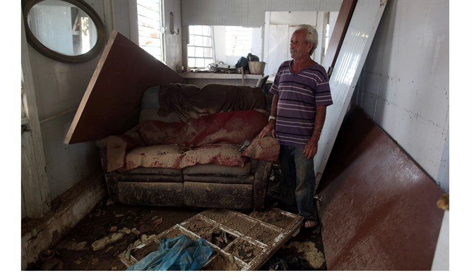 Man stands in rubble of house damaged by Hurricane Maria