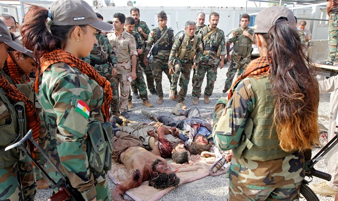 Kurdish Peshmerga fighters stand by the bodies of ISIS terrorists killed near Kirkuk