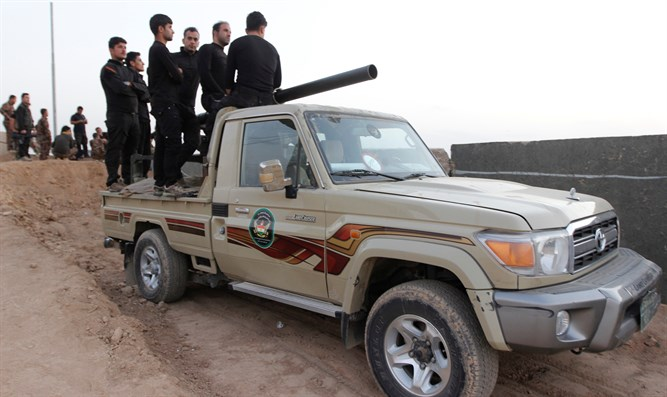 Kurdish Peshmerga fighters ride in vehicle Southwest of Kirkuk