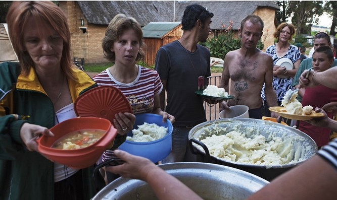 Residents of squatter camp for poor white South Africans line up for communal meal at Coro