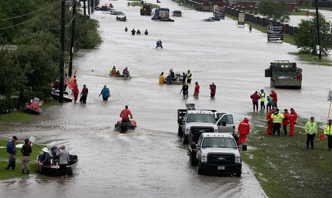 People making their way out of a neighborhood flooded by Hurricane Harvey