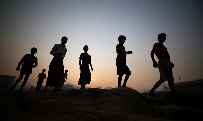 Rohingya refugees walk through Palong Khali refugee camp at sunris