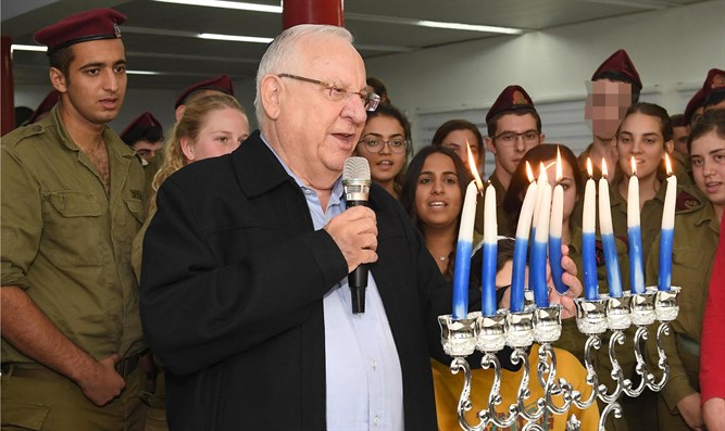 Rivlin lighting Hanukkah candles with soldiers