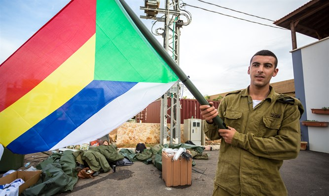 Druze IDF soldier waves the Druze flag in Israel's north