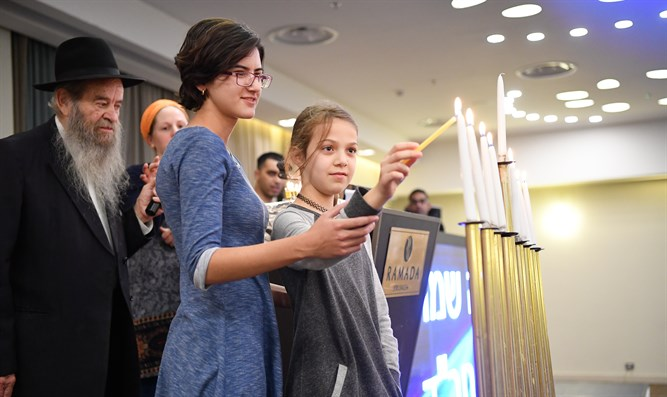 Ruth Zagha lights the 8th candle with Reut Salomon at the Colel Chabad Chanuka Retreat in