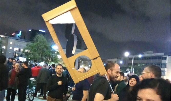 Man carries mock guillotine at protest
