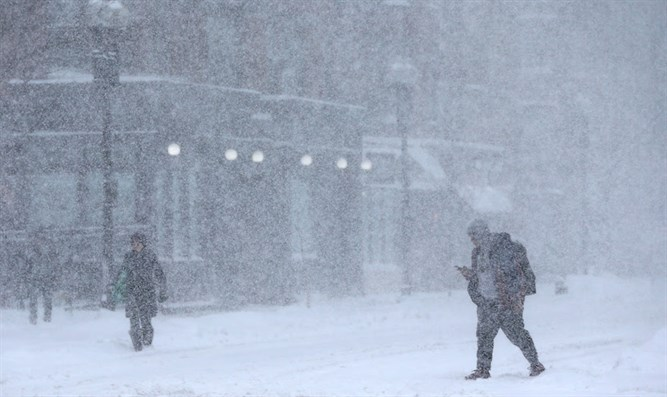 Pedestrians walking down Massachusetts Avenue during a massive winter storm in Boston, Mas