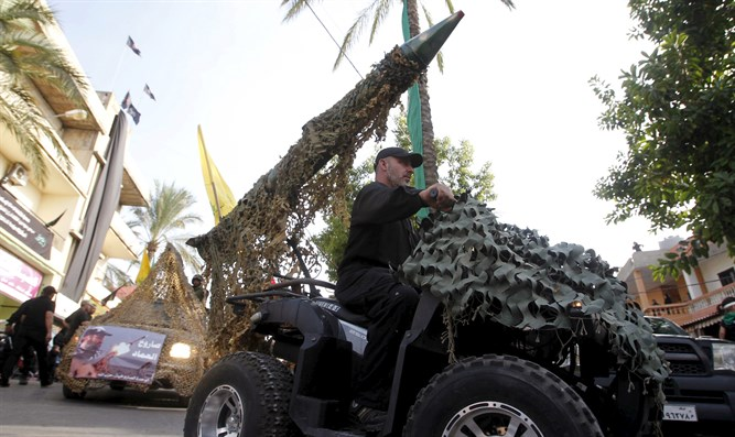Hezbollah member drives 4-wheel motorbike mounted with mock rocket