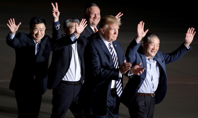Three Americans formerly held hostage in North Korea gesture next to Trump