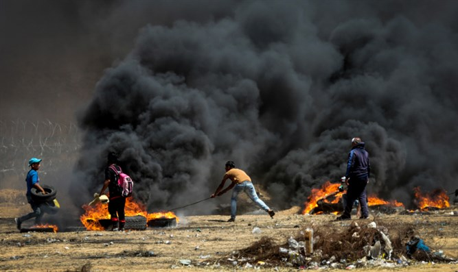 Arab rioters hurl flaming tires at Israel's fence along Gaza border