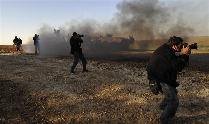 Foreign photographers take pictures of Israeli troops outside northern Gaza