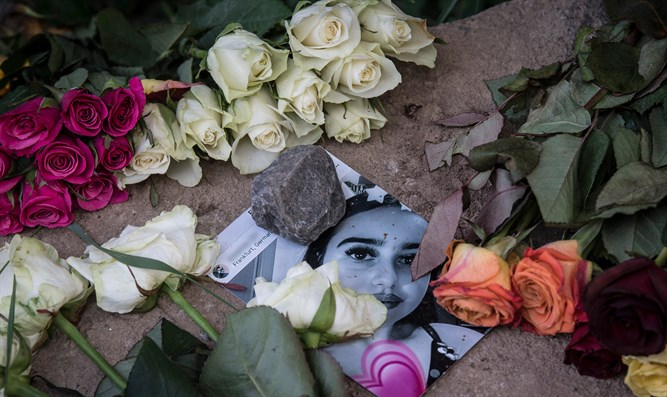 A picture of Susanna Maria Feldman is placed among flowers at a makeshift memori