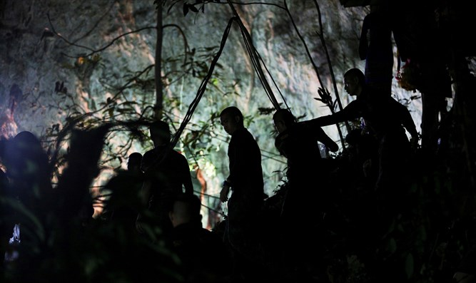 Military personnel are seen in front of the Tham Luang cave