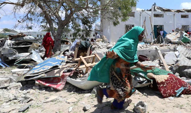Woman runs past debris at site of blast in district office of Hawlwadag in Mogadishu