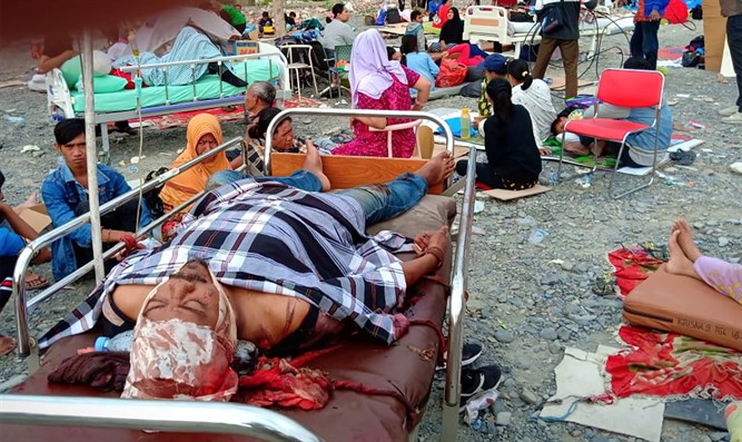 Earthquake survivors rest on beds outside a hospital in Palu, Sulawesi Island
